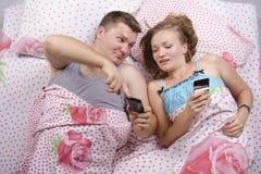Le type montre une fille dans le téléphone se situant dans le lit Images libres de droits