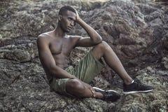 Le type noir s'assied sur le rivage rocheux image stock