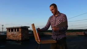 Le type peint un tableau Sur le toit clips vidéos