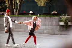Le type positif de hippie et son amie de mulâtre tiennent des mains et la promenade ensemble dans la rue, étant dans la bonne hum Images libres de droits