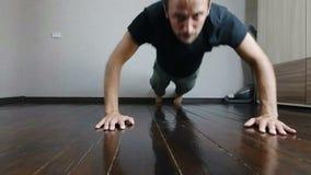Le type a poussé outre du plancher avec un visage fatigué tendu le jeune homme s'exerce à la maison clips vidéos
