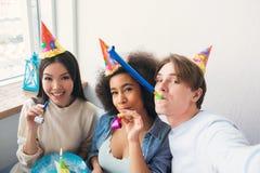 Le type prend un selfie avec ses deux amis Ils célèbrent l'anniversaire afro-américain de filles Les gens portent l'anniversaire Photo stock
