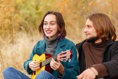 Le type ressemble à une fille jouant sur une ukulélé dans le plan rapproché de forêt d'automne photographie stock libre de droits