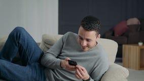 Le type rit le mensonge sur le sofa avec le téléphone clips vidéos