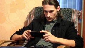 Le type s'asseyant avec le téléphone à la maison banque de vidéos