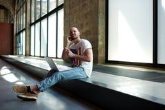 Le type s'asseyant dans le couloir attendant leur tour à l'université pour un examen Photographie stock