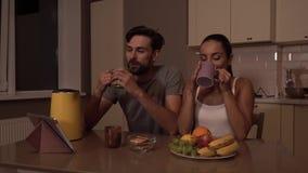 Le type s'assied dans la chaise et regarde la fille Elle le regarde trop et boit de la tasse Ils sourient à chacun banque de vidéos