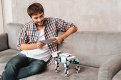 Le type s'assied sur le divan avec un comprimé et un robot Il lit quelque chose sur le comprimé Image stock