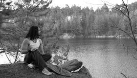 Le type s'assied sur la haute banque au-dessus du lac Détendez en nature Photos stock