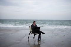 Le type s'assied sur la jetée par la mer et parle au téléphone Images stock