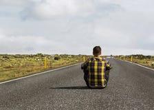 Le type s'assied sur la route en Islande photographie stock libre de droits