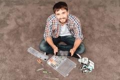 Le type s'assied sur le plancher À côté de lui est un rhinocéros de robot, les pièces de robots et les outils Photographie stock libre de droits