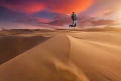 Le type sautant dans le désert sur une dune de sable au coucher du soleil photographie stock libre de droits