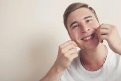 Le type se brosse les dents avec un fil dentaire Images stock