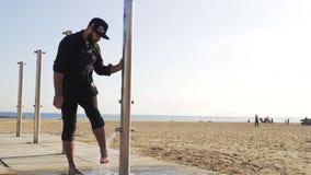 Le type se lave les pieds du sable dans la douche près de la plage banque de vidéos