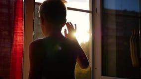 Le type se tenant près de la fenêtre et ondulé sa main Coucher du soleil banque de vidéos
