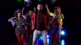 Le type se tient dans la tristesse autour d'une foule des personnes gaies dansant dans leur disco Fond noir Mouvement lent banque de vidéos