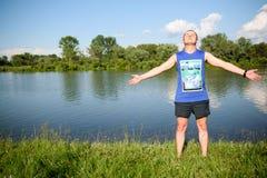 Le type se tient sur la banque de la rivière un été ensoleillé d Images libres de droits