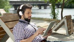 Le type se trouve sur le banc et écoute la musique par des écouteurs Également il tient le comprimé et dactylographie sur l'écran clips vidéos