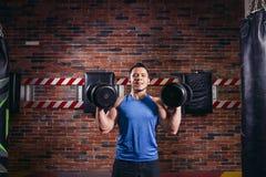 Le type sportif exécutent l'exercice avec des haltères, dans le gymnase images libres de droits