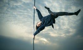 Le type sportif font les éléments acrobatiques sur le pylône train sportif d'homme sur le poteau images libres de droits