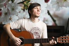 Le type sur le lit jouant la guitare classique photos libres de droits