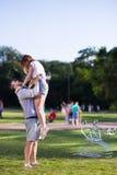 Le type tient son amie en parc Photographie stock