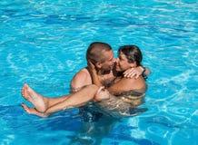 Le type tient une fille sur des mains tout en se tenant dans la piscine Images stock