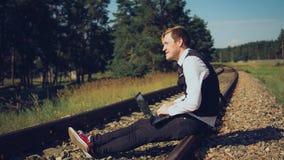 Le type travaille à un ordinateur en nature un temps clair ensoleillé Pour un ordinateur portable sur la rue, le concept de trava image stock