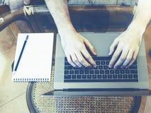 Le type travaille dans le bureau, sur le bureau d'ordinateur portable, un carnet avec Photos libres de droits
