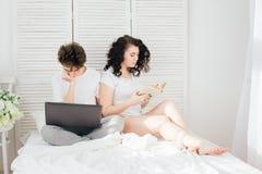 Le type travaille pour un ordinateur portable, fille lit un livre Photographie stock