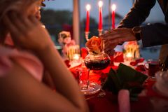 Le type verse le thé dans une tasse à son amie Table de dîner romantique de lueur d'une bougie Image libre de droits