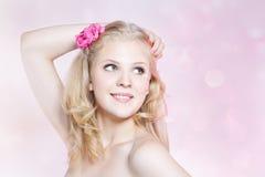 Le ung kvinna med rosa blommor arkivbild