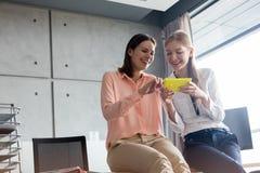 Le unga affärskvinnor som i regeringsställning använder mobiltelefonen Royaltyfri Bild