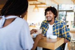 Le unga afrikanska par som sitter p? en tabell p? ett kaf? som dricker kaffe och tillsammans talar fotografering för bildbyråer