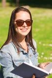 Le unga flickan med boksammanträde parkera in Royaltyfri Fotografi