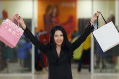 Le unga flickan med deras händer upp och packar i galleria arkivfoto
