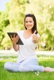 Le unga flickan med minnestavlaPC:n som sitter på gräs Royaltyfri Bild