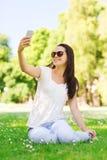 Le unga flickan med smartphonesammanträde parkera in Royaltyfria Foton