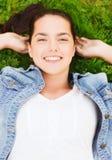 Le unga flickan som ligger på gräs Arkivbild
