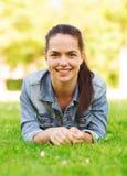 Le unga flickan som ligger på gräs Arkivfoton