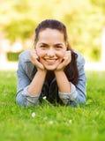 Le unga flickan som ligger på gräs Royaltyfria Bilder