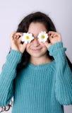 Le unga flickan som täcker henne ögon med blommor Arkivfoton