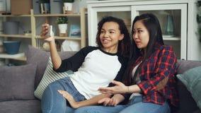 Le unga kvinnor asiat och afrikansk amerikan som gör den online-videopd appellen som ser smartphoneskärmen som talar och lager videofilmer