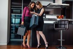 Le unga kvinnor som bär formell elegant kläder som ser in i anseende för shoppingpåse i den moderna lägenheten royaltyfria foton