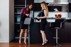 Le unga kvinnor som bär formell elegant kläder som ser in i anseende för shoppingpåse i den moderna lägenheten fotografering för bildbyråer