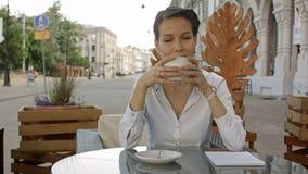 Le unga kvinnor som dricker kaffe eller te och skvallrar på det utomhus- kafét stock video