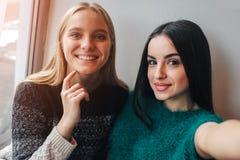 Le unga kvinnor som tar selfie, medan dricka kaffe inomhus på lunchmötet Arkivfoton