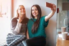 Le unga kvinnor som tar selfie, medan dricka kaffe inomhus på lunchmötet Royaltyfri Fotografi
