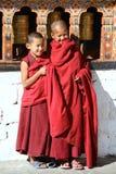 Le unga munkar som står vid de religiösa bönhjulen på Paro Rinpung dzong, Paro, Bhutan Royaltyfri Fotografi
